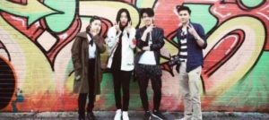 A group of Chinese students posing in front of a graffitied wall in Brighton