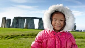 Young Chinese girl visiting World Heritage tourism site Stonehenge
